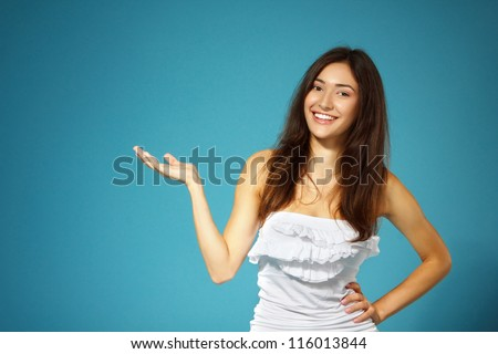 beautiful cheerful teen girl show something with her hand over blue background