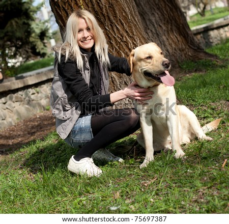 Beautiful cheerful woman sitting with her dog in the park