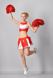 Beautiful cheerleader on grey background