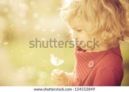 Beautiful child blowing away dandelion flower in spring - stock photo