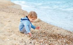 Beautiful child boy playing with sand and running in the water on sunset. Boy throwing rocks. Vacation and summer holidays. Concept authentic lifestyle on vacation on a wild beach