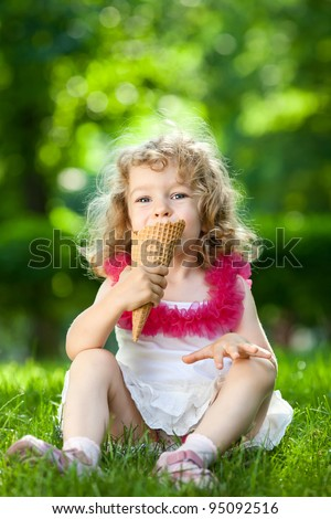 Beautiful child eating ice-cream outdoors in spring park against natural green background