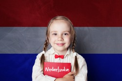 Beautiful child girl smiling and holding book in Netherlandish language school. Learning Dutch