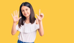Beautiful child girl wearing casual clothes showing and pointing up with fingers number seven while smiling confident and happy.