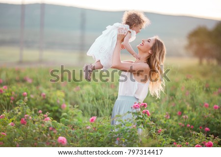 Beautiful child girl with pretty young mother are wearing casual clothes are walking in spring garden with pink blossom roses