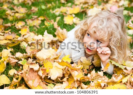 Beautiful child lying on yellow maple leaves in autumn park