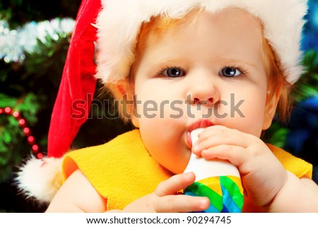 Beautiful child sitting with presents against Christmas background.