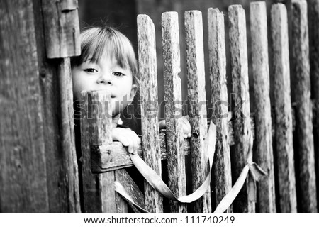 Beautiful child standing near vintage rural fence (Black-and-white photo with high contrast)
