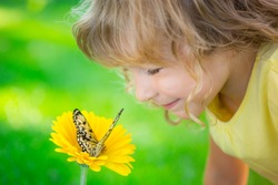 Beautiful child with butterfly in spring park. Happy kid playing outdoors