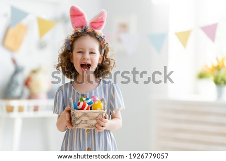 Beautiful child with painting eggs. Happy family preparing for Easter. Cute little girl is wearing bunny ears.