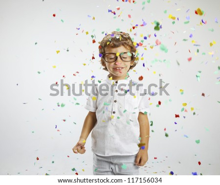 Beautiful child with rimmed glasses and confetti. Portrait of child wrapped with confetti