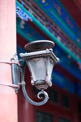 Beautiful Chinese bronze sculpture lamp at the wooden pole under the traditional eaves