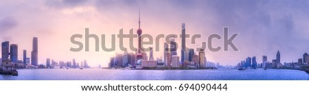 Beautiful chinese cityscape of Shanghai's skyline with the city lights and tower on the Huangpu River bay, Shanghai, China. #694090444