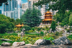 Beautiful Chinese garden and pond surrounding a pagoda contrasted by Sydney city in the background. Chinese Garden of Friendship, Sydney, Australia.