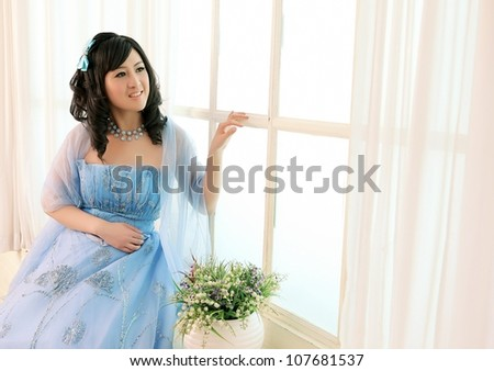 Beautiful Chinese girl standing aside window happily