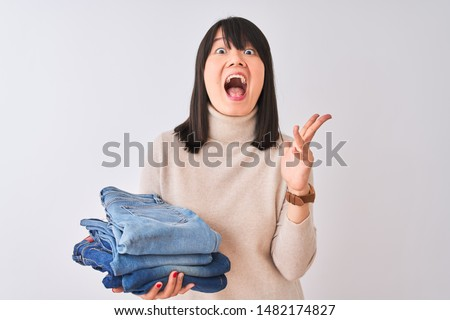Beautiful Chinese shopkeeper woman holding folded jeans over isolated white background very happy and excited, winner expression celebrating victory screaming with big smile and raised hands