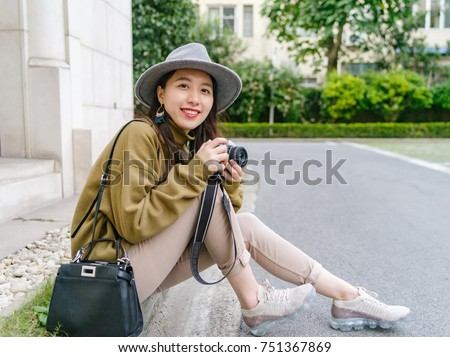 Beautiful Chinese woman sit at the edge of street, smiling with camera in hand, travel concept.