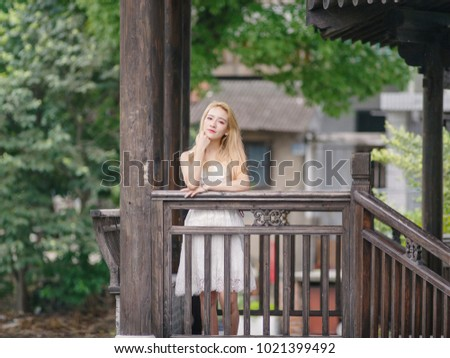 ff8cecfdd Beautiful Chinese young girl wearing a white dress in summer park. Outdoor  fashion portrait of