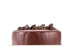 beautiful chocolate cake isolated on a white background, side view. many candies decorating the top of the dessert