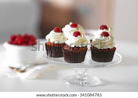 Beautiful chocolate cupcakes with cream and raspberry on table #341084783