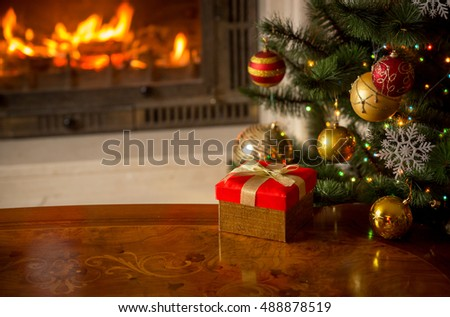 Stock Photo Beautiful Christmas background with present, Christmas tree and burning fireplace. Place for text