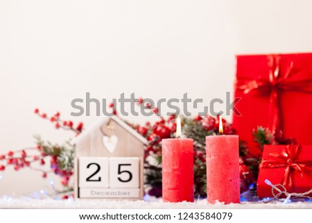 Beautiful Christmas Background with wooden block Calendar and Red Decorations - candles, gift boxes, Christmas tree, Garland. Calendar with the date of December 25 - Holiday greeting Card Template     #1243584079