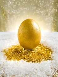 Beautiful christmas card with golden egg  with snow and gold pollen on the background of golden light bokeh. Christmas present. Christmas holiday celebration