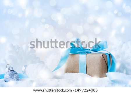 Beautiful Christmas composition with gift or present box in snow and decoration against holiday lights background.