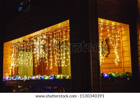 Beautiful Christmas decorations outside the house at night. House decorated with glowing lights for Christmas. #1530340391