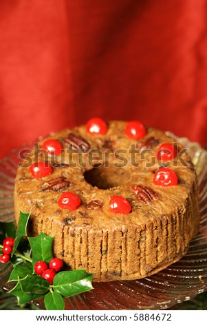 Beautiful Christmas fruitcake with holly garnish on a red draped silk background. Vertical with room for text.
