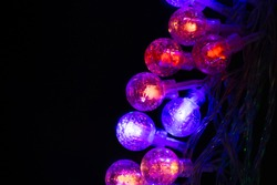 Beautiful Christmas garlands with led lights in glass balls on a black background