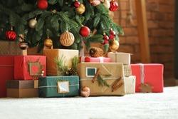 Beautiful Christmas gifts under fir tree on floor in room