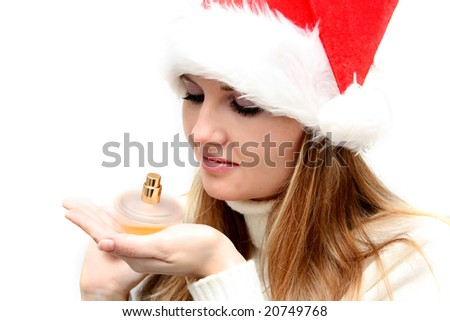 Beautiful christmas girl in santa hat holding bottle of perfume
