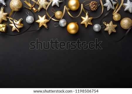 Beautiful christmas golden silver deco baubles on dark black background. Flat lay design. Copy Space. Horizontal.