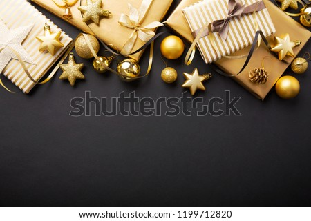 Beautiful christmas golden silver deco baubles with gifts on dark black background. Flat lay design. Copy Space. Horizontal. #1199712820