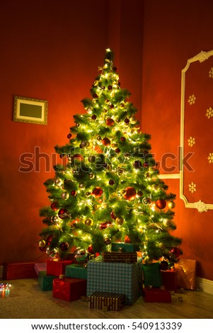 Beautiful Christmas living room with decorated Christmas tree, gifts and fireplace with the glowing lights at night #540913339