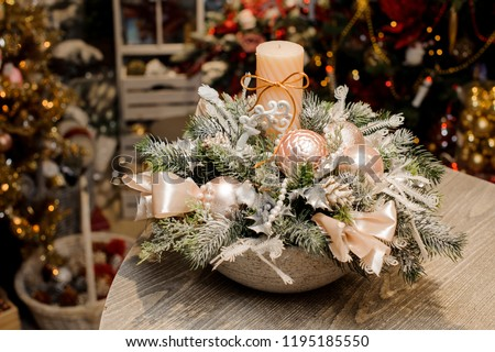 Beautiful Christmas table composition in vase made of fir tree covered with artificial snow, beige balls and bows, candle and beads against the festive interior #1195185550