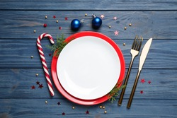 Beautiful Christmas table setting on blue wooden background, flat lay