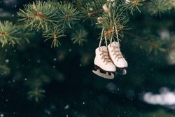 Beautiful christmas tree decoration small ice skates on the rope on a branch.