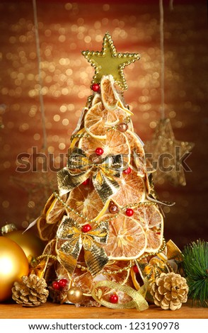 beautiful christmas tree of dry lemons with decor, on shine background