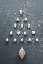 Beautiful Christmas tree shaped out of white festive ornaments on the old rustic grey background, dusted with fake snow