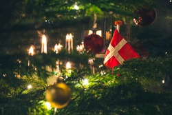 Beautiful Christmas tree with Danish flag, Scandinavian candelier, ornaments and lights, Christmas decorations and background