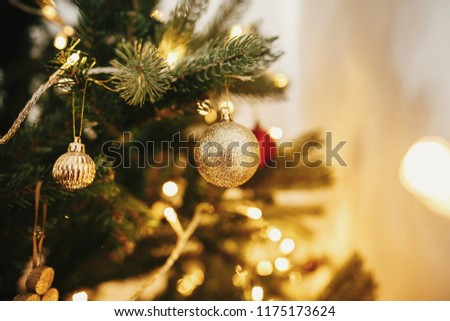 beautiful christmas tree with ornaments, golden lights in festive room. red and gold balls on pine tree branches. decor for winter holidays. atmospheric moment