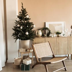 Beautiful Christmas tree with toys, baubles and homemade paper gift boxes. Living room decorated for Christmas / New Year celebration. Modern interior design concept with rattan chair, beige wall.