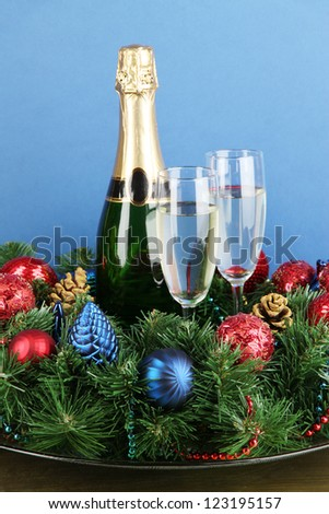 Beautiful Christmas wreath in composition with champagne on blue background