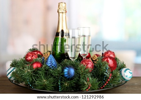 Beautiful Christmas wreath in composition with champagne on room background