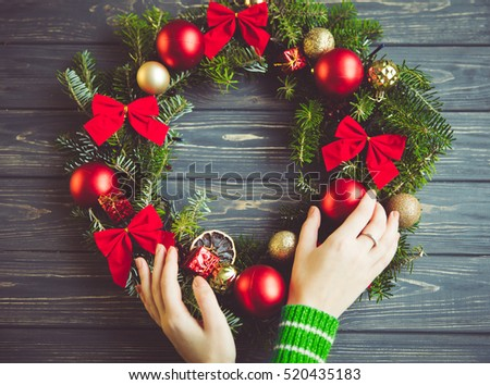 Beautiful Christmas wreath in woman hands. The concept of preparation for the holidays. Festive interior decor