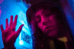 Beautiful cinematic portrait of stylish young woman in neon lighted window with rain drops. Bright neoned colors. Caucasian model, musician outdoors. Youth culture, scary mist style and music concept.
