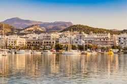 Beautiful city landscape of the port, yachts, azure sea water against the blue sky in the evening, Rethymno Harbor, Crete, Greece.