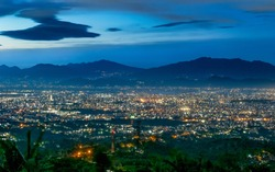 Beautiful city light at night, seen faraway from top of the hilll, also showing shadow of mountain in the background, captured in Bandung, Indonesia